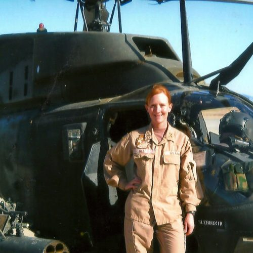 2015 US Army Women's Foundation Hall of Fame Distinguished Flying Cross Recipient Inductee CW3 Lori Hill standing in front of her helicopter